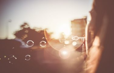 girl-blowing-bubbles-in-the-sun